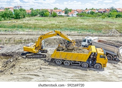 Big excavator is filling a dump truck with soil at construction site, project in progress.