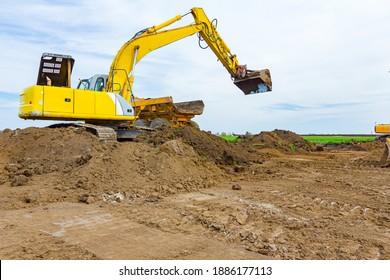 Der große Bagger füllt einen Müllwagen mit Boden auf dem Baugelände, das Projekt läuft.