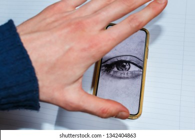 big eye on the smartphone screen watches its user. hand trying to close the camera of the smartphone, selective focus. Big brother is watching you concept
