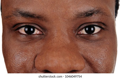 The big eyes of an African American man in a close up image, lookingstrait into the camera, isolated for white background