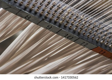 Big factory industrial machine feeding huge amounts of material in threads through plastic tubes in this commercial equipment with numbers