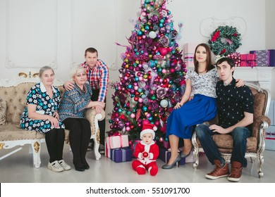 big family and child in a suit of Santa Claus sitting by the Christmas tree