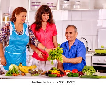 Big family cooking at kitchen. Grandfather and grandmother with adult daughter.