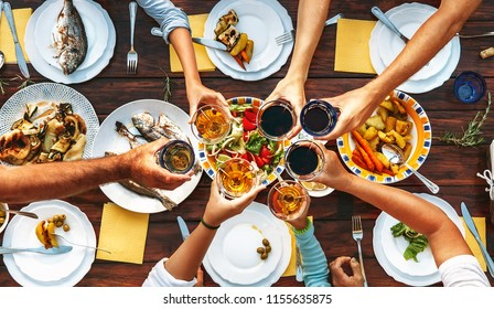 Big family dinner. Top view on served table and hands with clinking goblets
