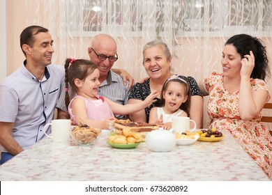 big family drinking tea in dining room