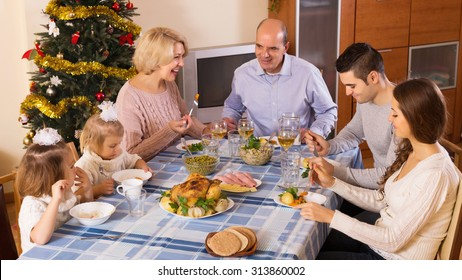 Big Family At Festive Table Near Christmas Tree. Focus On Young Woman