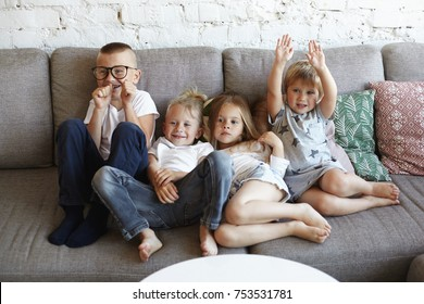 Big family of four cheerful excited children sitting on comfortable sofa in living room, playing words guessing game. Happy emotional Caucasian siblings fooling around at home on big grey couch