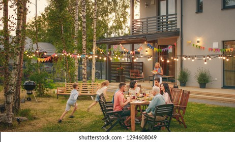 Big Family Garden Party Celebration, Gathered Together at the Table Family, Friends and Children. People are Drinking, Passing Dishes, Joking and Having Fun. Kids Run Around Table. - Shutterstock ID 1294608049