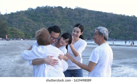 The big family are happily hugging each other on the beach.