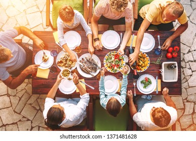Big family have a dinner with fresh cooked meal on open garden terrace