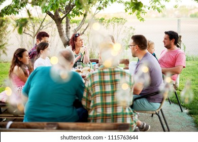Big family having a meal outside at the table near the farm on a chatting and having fun.