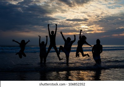 big family jumping on the beach at dusk