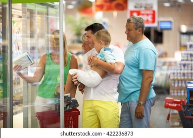 Big family with kid choosing food in supermarket