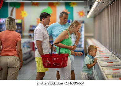 Big family with parents, grandparents and child shopping for food in the supermarket. Little boy exploring the freezers