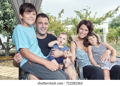 Big family. Parents with three children outdoors. Two daughters and one son.