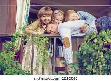 Big family peeks out from the balcony of their house. The man is lying on the railing, twined with green plants, and the children are hugging him
