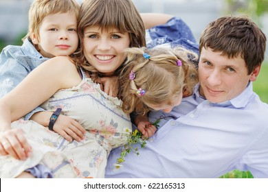 Big family posing in front of the camera at a picnic. Mom, Dad, son and daughter are lying on a plaid in the green grass
