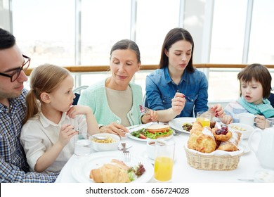 Big family sitting by table in restaurant and eating breakfast