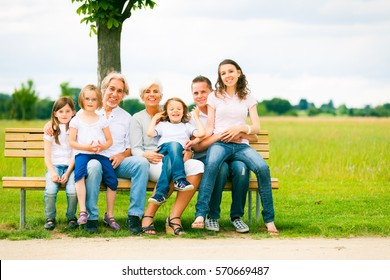 Big Family Sitting On A Bench