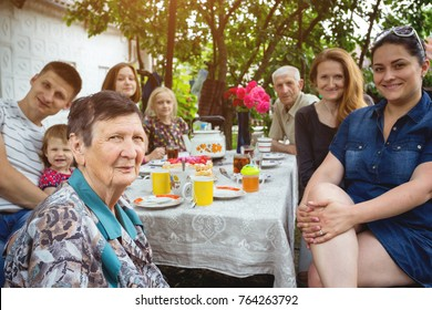 Big Family Sitting At A Table In The Garden