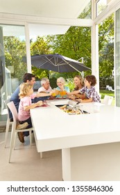 Big family is sitting at the table having lunch and toasting with juice