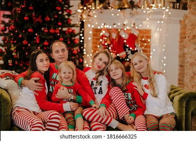 Big family of six in Christmas pyjamas sitting together on a sofa against Christmas background.