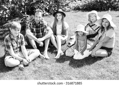 Big family - smiling father, mother, grandma ,son and two daughters on the green grass in the park.  Summer holiday.