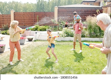 Big family spending time in backyard shooting water gun on hot sunny weather, copy space