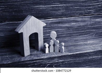 Big family is standing near the house. Wooden figures of persons stand near a wooden house. The concept of a couple in love, cohabitants, parents, buyers and sellers at home. They live in the house