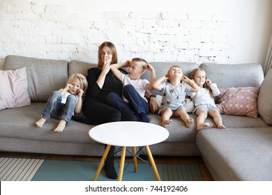 Big family of three spoiled little boys and one girl fooling around, crying and covering ears, their confused mother going crazy, making faces instead of calm them down. Single mother of many kids