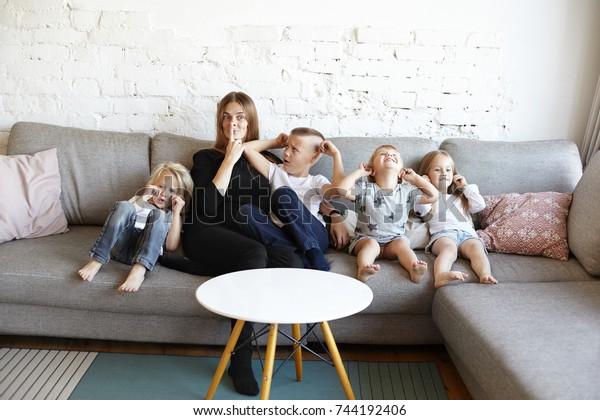 La grande famille de trois petits garçons gâtés et d'une fille qui se baladent, pleurant et couvrant les oreilles, leur mère confuse devenant folle, faisant des visages au lieu de les calmer. Mère célibataire de nombreux enfants