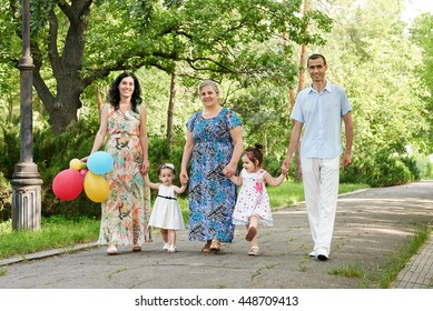 big family walk in summer city park, parents with child and grandmother, summer season, green grass and trees