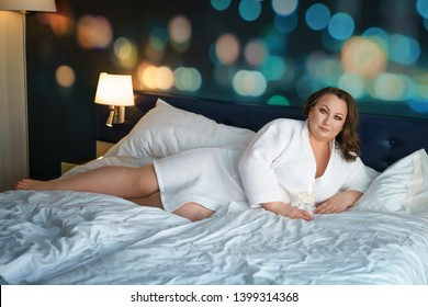 big fat woman in white robe lying on the bed , relax in the hotel