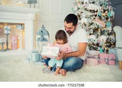 Big father and happy little daughter open New Year's gifts near the Christmas tree