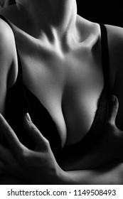 big female breasts in black bra closeup on dark background, monochrome