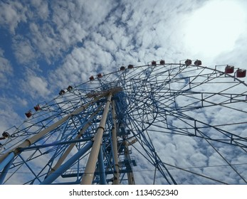 Big Ferris wheel, summer day in city park. Metal constructions on blue sky with clouds. View from bottom. Black Sea coast, Russia.