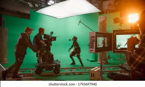 In the Big Film Studio Professional Crew Shooting Blockbuster Movie. Director Commands Cameraman to Start shooting Green Screen CGI Scene with Actor Wearing Motion Tracking Suit and Head Rig - Shutterstock ID 1793697940