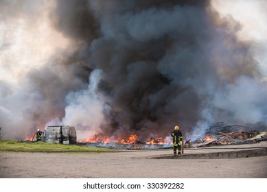 Big fire of buildings and cars. Black smoke coming up to the sky. Firemen at work. Bestseller photo representing explosion, fireman, fire, accident, crash, catastrophe, disaster, danger and insurance.