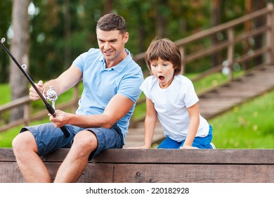 It is a big fish! Happy father and son fishing together while little boy looking excited and keeping mouth open
