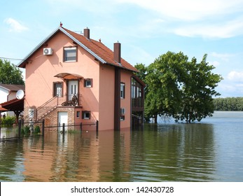 big flooded house with blue sky and white clouds in high water