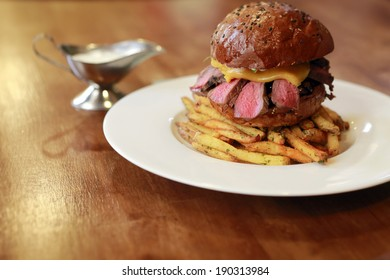 big fresh beef burger with French fries on the wood table