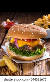 Big fresh made Burger on rustic wooden background (with French Fries)