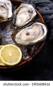Big fresh oysters on ice with lemon.