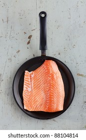 Big fresh salmon steak in black frying pan on rustic diner table, taken directly from above.