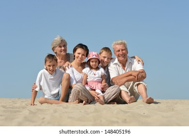 big friendly family relaxing on the sand together in the summer