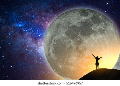 Big full moon, milky way, star, silhouette happy young woman on the mountain with detail of the milky way. Elements of this image furnished by NASA