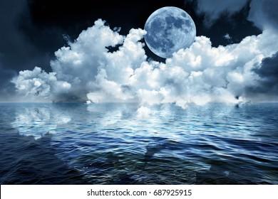 Big full moon in night sky over the ocean reflecting in calm water