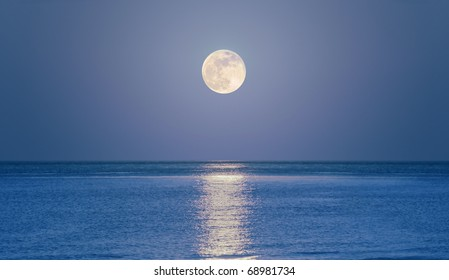 Big full moon is rising above the sea at dusk.