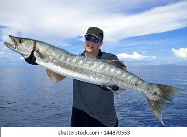 Big game fishing. Lucky  fisherman holding a giant barracuda