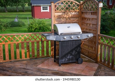 Big gas barbeque grill, stainless construction with black bottom stands at the wooden terrace corner. Water drops after heavy rain. Small red wooden house in green garden at background. Summer day